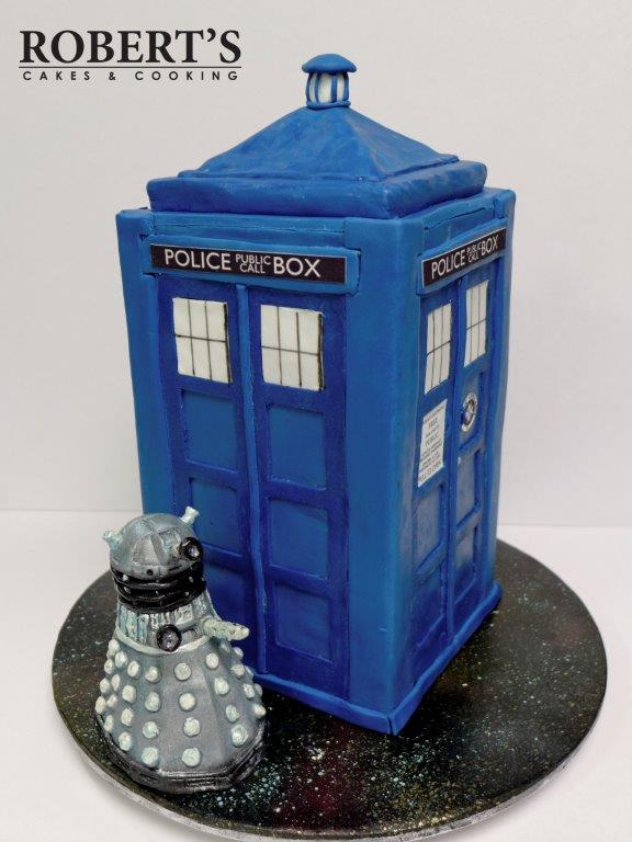 "Dr Who Tardis Cake | The TARDIS is Homemade fondant on an ""orange velvet"" cake filled and covered in dark chocolate orange ganache. The board is covered in white fondant then baked for 10 minutes at 80C to set it hard before it was airbrushed with food colour to look like a galaxy. The signage is icing sheets printed with edible ink. I made the Dalek from homemade modelling chocolate. 